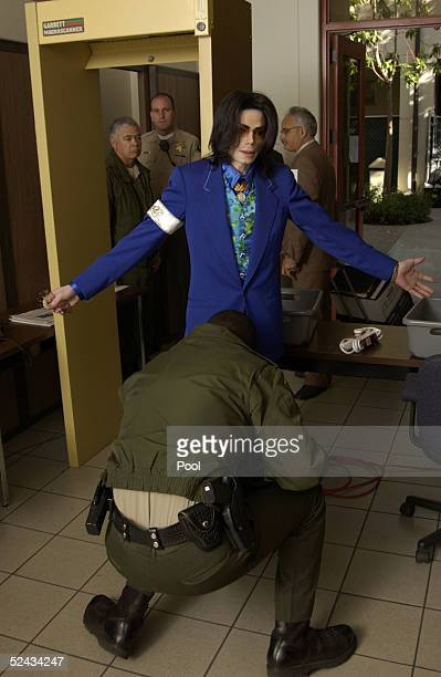 Singer Michael Jackson is checked with a metal detector by a sheriff's deputy outside the courtroom at Santa Barbara County Courthouse as he arrives...