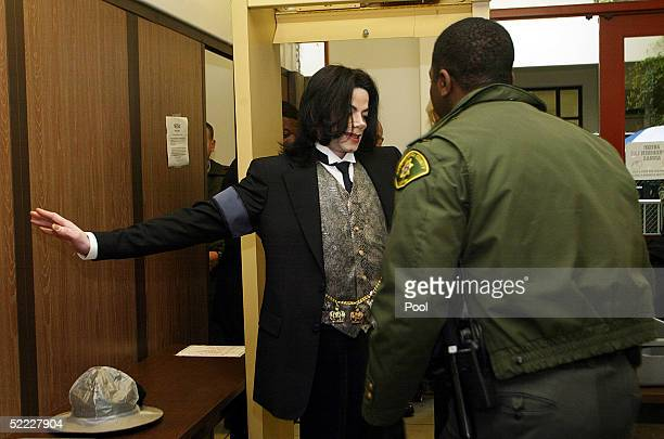 Singer Michael Jackson is screened by a sheriff's deputy as he arrives at the Santa Barbara County Courthouse for continuation in the jury selection...
