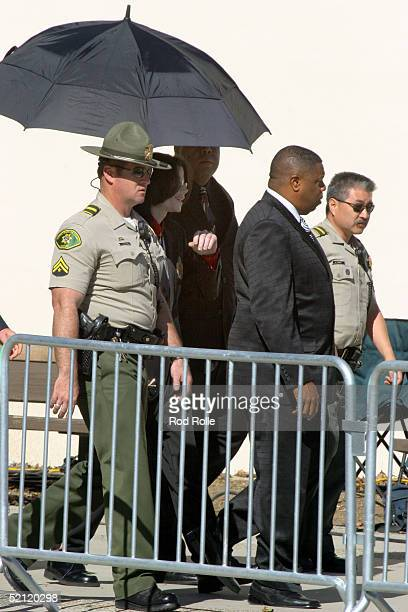 Singer Michael Jackson leaves the Santa Barbara Superior Courthouse surrounded by security personnel after the second day of jury selection in his...