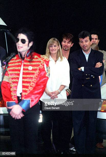 Singer Michael Jackson signs autographs for fans as wife Debbie Rowe looks on on July 10 1997 in Sheffield England