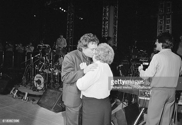 Singer Michel Sardou gives his mother Jackie a kiss following his last show at the Palais des Congres in Paris.