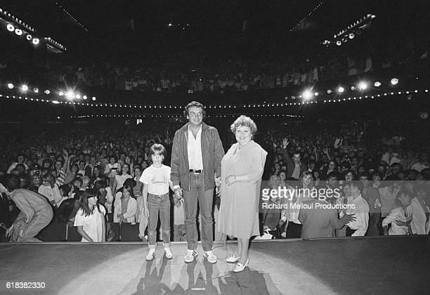 Singer Michel Sardou poses on stage with his mother Jackie and his son Romain during a concert for his fan club at L'Olympia in Paris.