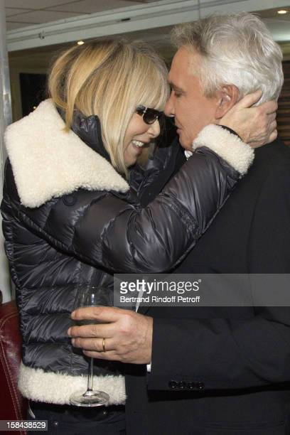 Singer Michel Sardou shares a light moment with actress Mireille Darc in his dressing room following his show at Palais Omnisports de Bercy on...
