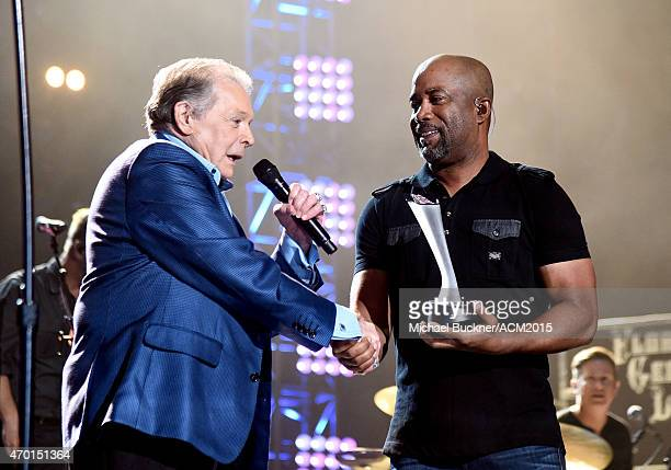 Singer Mickey Gilley accepts the Triple Crown Award from singer Darius Rucker onstage during ACM Presents Superstar Duets at Globe Life Park in...
