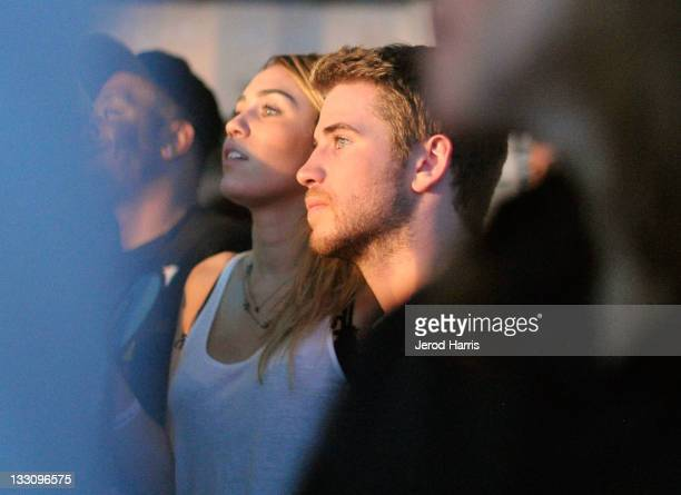 Singer Miley Cyrus and actor Liam Hemsworth enjoy the Drake performance the launch of Google Music hosted by TMobile at Mr Brainwash Studio on...