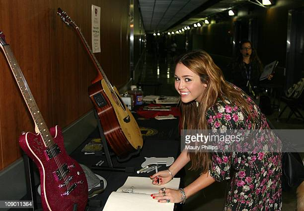 Singer Miley Cyrus poses at the MusiCares signing booth during The 53rd Annual GRAMMY Awards at Staples Center on February 11 2011 in Los Angeles...