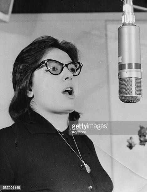 Singer Nana Mouskouri singing into a microphone in a music studio Paris France February 16th 1961