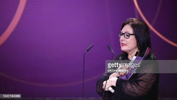 Singer Nana Mouskouri stands on stage with her award during the Echo Music Awards ceremony in Berlin Germany 26 March 2015 Mouskouri was awarded for...