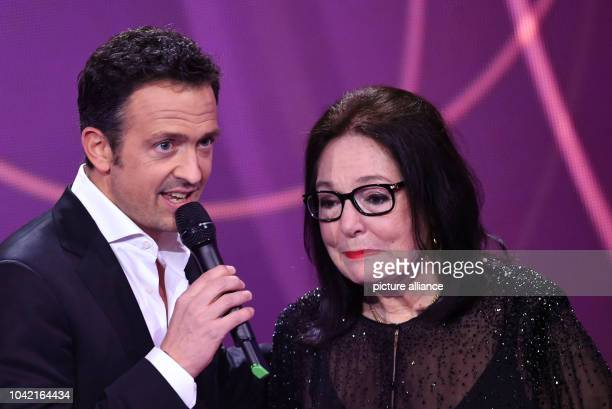 Singer Nana Mouskouri stands on stage with her award next to German musician Till Broenner during the Echo Music Awards ceremony in Berlin, Germany,...