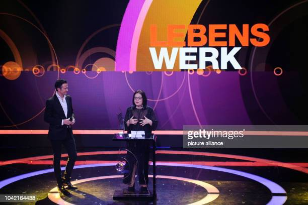 Singer Nana Mouskouri stands on stage with her award next to German musician Till Broenner during the Echo Music Awards ceremony in Berlin Germany 26...