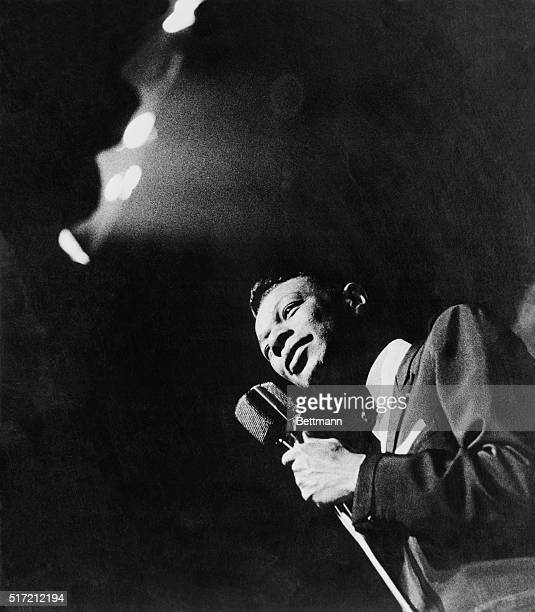 Singer Nat King Cole holding microphone during a concert