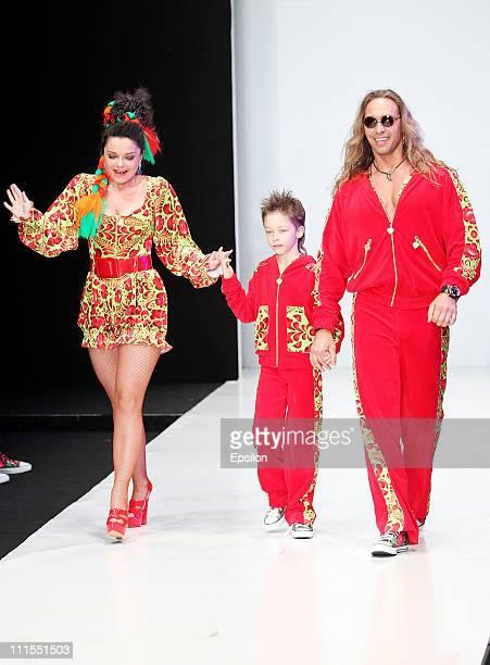Singer Natasha Koroleva her husband model Tarzan and their son wear a creation by designers Yana and Anastasia Shevchenko by YanaStasia on day 5 of...