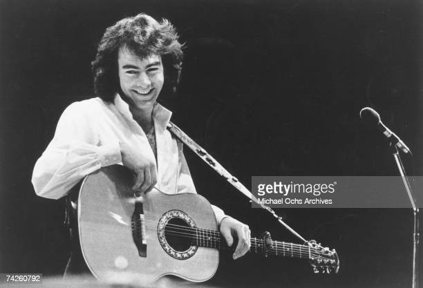 Singer Neil Diamond performs onstage with an acoustic guitar in circa 1971