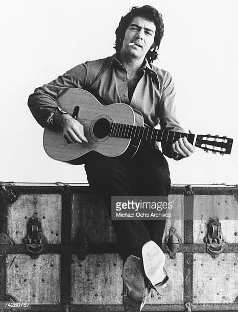 Singer Neil Diamond poses for a portrait with an acoustic guitar in circa 1970