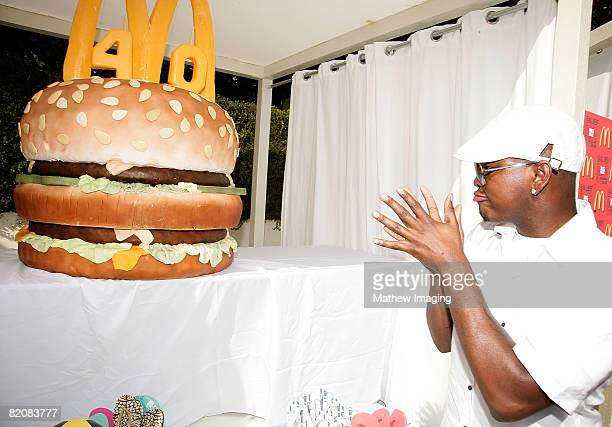 Singer NeYo poses beside a giant burger during the McDonald's Big Mac 40th Birthday Party at Project Beach House in Malibu California on July 27 2008