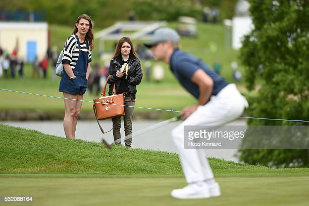 Singer Niall Horan of One Direction reacts to his putt on the 4th green watched by two girls during a ProAm round prior to the start of the Dubai...