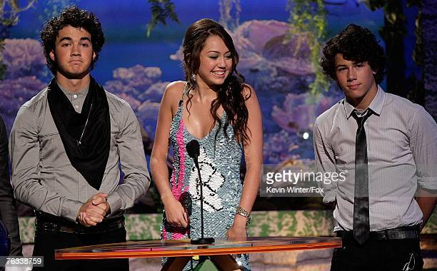 Singer Nick Jonas actress Miley Cyrus and singer Kevin Jonas present the 'Choice RB Track' award onstage during the 2007 Teen Choice Awards held at...