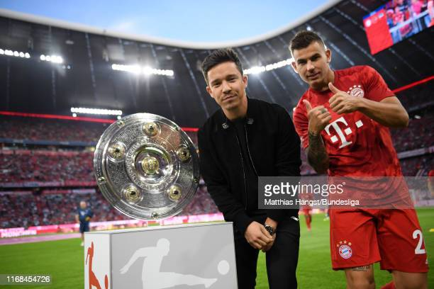 Singer Nico Santos poses for a picture next to the Bundesliga trophy as Lucas Hernandez of FC Bayern Munich reacts prior to the Bundesliga match...