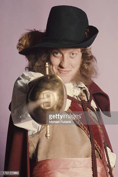 Singer Noddy Holder of English glam rock group Slade posing in a cavalier costume and pointing a sword London 1974