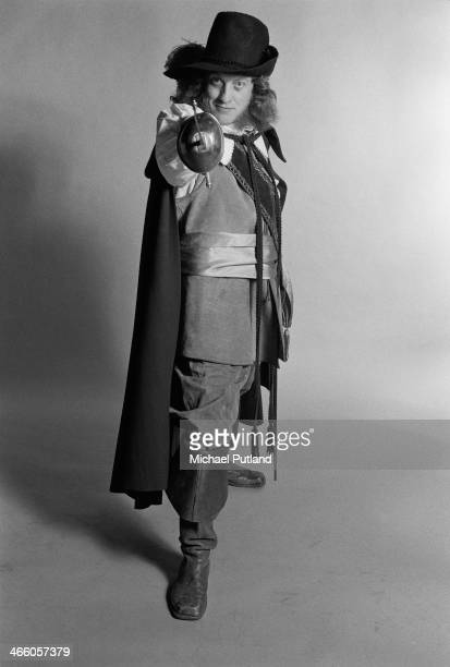 Singer Noddy Holder of English rock group Slade posing in a cavalier costume and pointing a sword at the camera London 1974