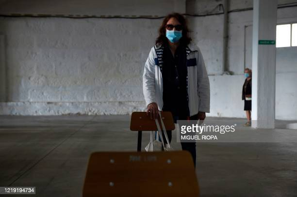 A singer of the Apostol Santiago choir wearing a face mask arrives to attend the first rehearsal after the loosening of a national lockdown to stop...