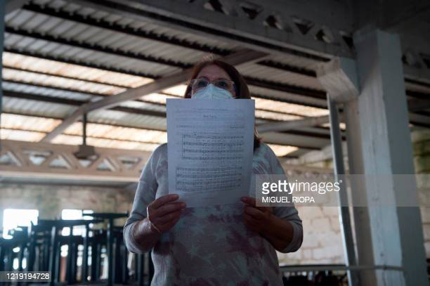 A singer of the Apostol Santiago choir wearing a face mask attends their first rehearsal after the loosening of a national lockdown to stop the...