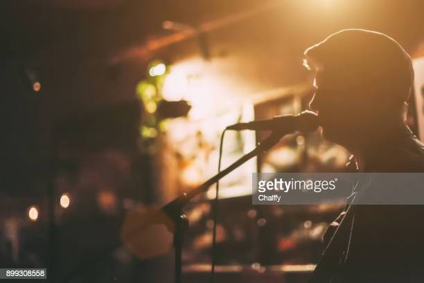 singer on a stage - acoustic guitar stock pictures, royalty-free photos & images