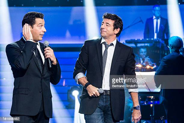 Singer Patrick Bruel and impersonator Laurent Gerra both impersonating singer Gilbert Becaud perform during the live broadcast on public channel...