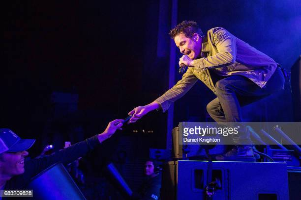 Singer Patrick Monahan of Train takes a cell phone from a fan to take a selfie on stage at Mattress Firm Amphitheatre on May 14 2017 in Chula Vista...