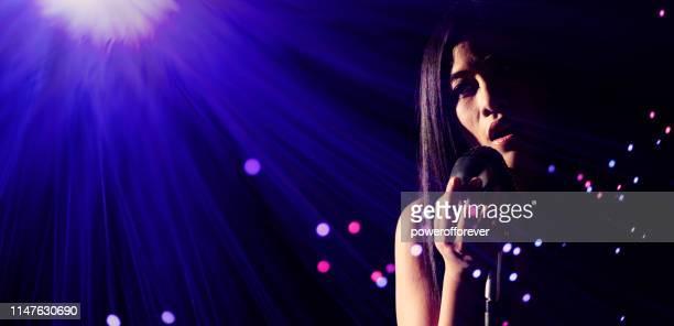 歌手がステージで歌を演奏する - シンガーソングライター ストックフォトと画像