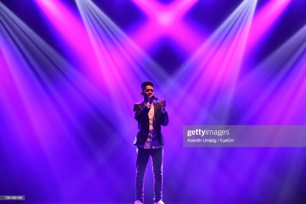 Singer Performing Against Illuminated Stage Lights : Stock Photo