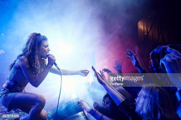 singer performing on stage reaching out to crowd - performance group stock pictures, royalty-free photos & images