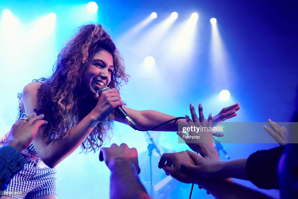 Singer performing on stage reaching out to crowd : Stock Photo