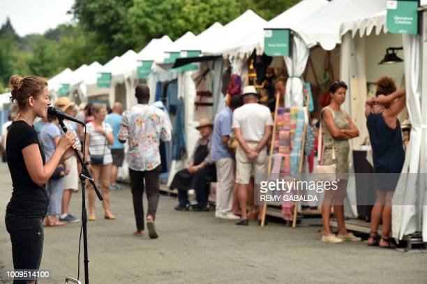 A singer performs as people walk in a street of Marciac on July 31 during the 41st edition of the Marciac Jazz Festival