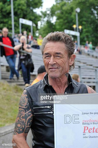 Singer Peter Maffay receives a cheque over Û 261490 for Peter Maffay Stiftung from Prof Peter Schwenkow of DEAG Deutsche Entertainment AG prior to...