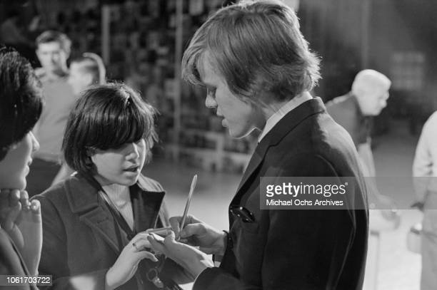 Singer Peter Noone of British pop group Herman's Hermits signs autographs while appearing on 'Hullabaloo' at NBC's Studio 8H in New York City 9th...