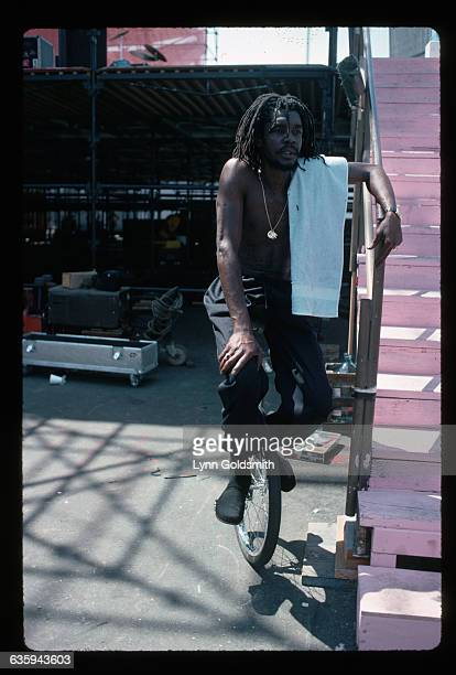 Singer Peter Tosh is shown seated on a unicycle apparently at an outdoor stage Undated