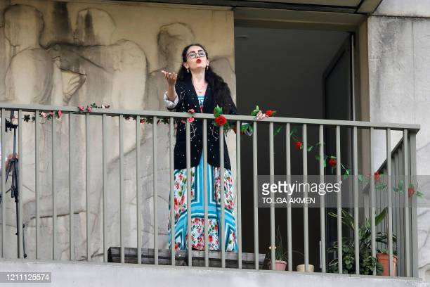 Singer Phoebe Haines performs on her balcony in East Village in Stratford, east London, on April 27, 2020 for her neighbours as British life...