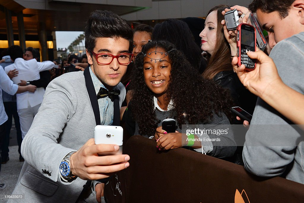 Singer Piero Barone (L) of the group Il Volo greets fans before signing copies of their new album 'We Are Love' at Santa Monica Place on June 12, 2013 in Santa Monica, California.