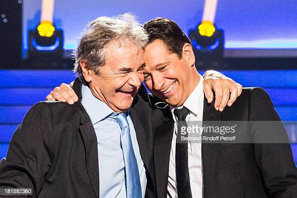 Singer Pierre Perret and impersonator Laurent Gerra impersonating Perret embrace after they performed during the live broadcast on public channel...