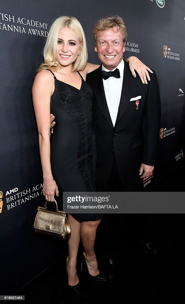 Singer Pixie Lott (L) and director Nigel Lythgoe attend the 2016 AMD British Academy Britannia Awards presented by Jaguar Land Rover and American Airlines at The Beverly Hilton Hotel on October 28, 2016 in Beverly Hills, California.