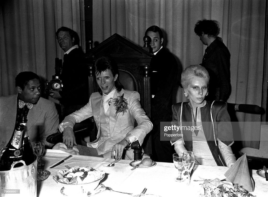Singer, Pop star David Bowie (centre) and his wife Angie at a party given by Bowie at the Cafe Royal following his last public concert at the Odeon Theatre, Hammersmith, Bowie announced that he plans to start a new career in films : News Photo