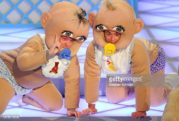 Singer presenter Florian Silbereisen and Stefan Mross perform in baby costumes during the MDR 'Winterfest der fliegenden Stars' at the Erdgas Arena...