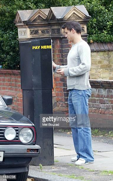 Singer Rachel Stevens's boyfriend puts change in the parking meter on August 12 2002 in Hampstead England