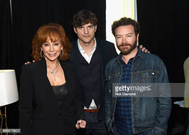Singer Reba McEntire and actors Ashton Kutcher and Danny Masterson pose backstage during the 2017 CMT Music awards at the Music City Center on June 7...