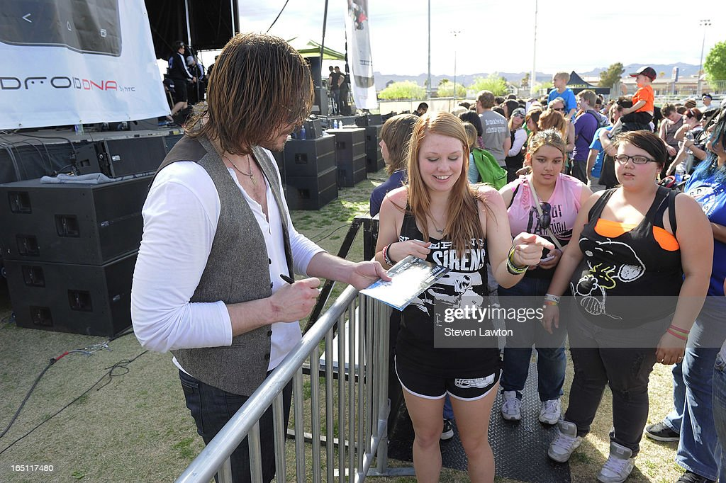 Singer Rick DeJesus (L) of the band Adelitas Way signs autographs after performing during the 18th annual Extreme Thing Sports & Music Festival on March 30, 2013 in Las Vegas, Nevada.