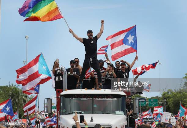 Singer Ricky Martin waves a flag as he joins with thousands of other people as they fill the Expreso Las Américas highway calling for the ouster of...