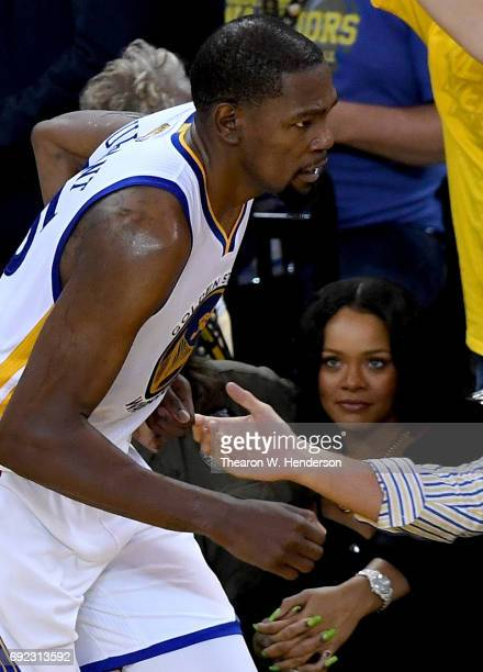 Singer Rihanna looks at Kevin Durant of the Golden State Warriors after he shoots a threepoint shot in Game 1 of the 2017 NBA Finals against the...