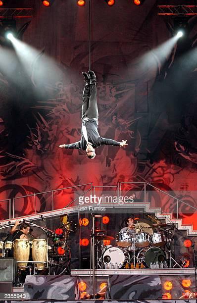 Singer Robbie Williams performs at Knebworth Park August 1, 2003 in Hertfordshire, England.