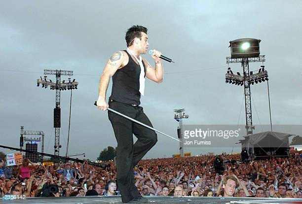 Singer Robbie Williams performs the first of three sold-out shows at rock venue Knebworth Park August 1, 2003 in Hertfordshire, north of London,...